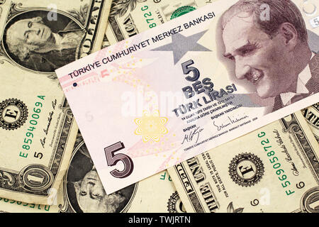 A close up image of a purple five Turkish lira bank note on a background of American one dollar bills in macro - Stock Photo