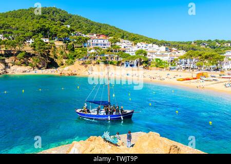 TAMARIU, SPAIN - JUN 2, 2019: Boat with divers sailing in beautiful bay near fishing village of Tamariu, Costa Brava, Spain. - Stock Photo