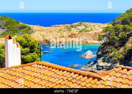 View of  Sa Tuna sea bay with orange tile roof in foreground, Costa Brava, Spain - Stock Photo