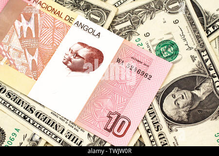 An red and white ten Angolan kwanza bank note on a background of American one dollar bills - Stock Photo