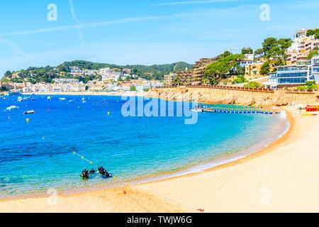 TOSSA DE MAR, SPAIN - JUN 3, 2019: Divers in water on beach in Tossa de Mar town, Costa Brava, Spain. - Stock Photo