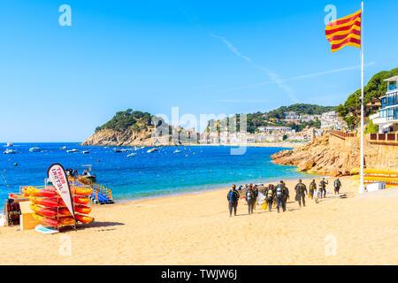 TOSSA DE MAR, SPAIN - JUN 3, 2019: Divers walking to water on beach in Tossa de Mar town, Costa Brava, Spain. - Stock Photo