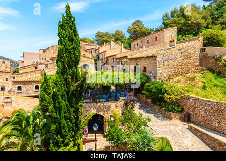 Restaurant in old town of Tossa de Mar with beautiful stone houses, Costa Brava, Spain - Stock Photo