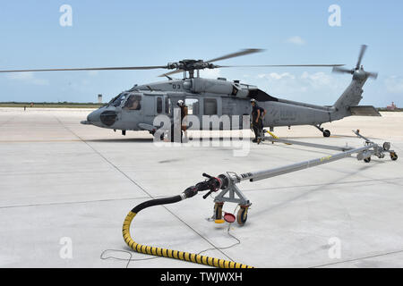 190620-N-KM072-003 (KEY WEST, Fla.) Naval Air Station Key West's MH-60 Seahawk search and rescue helicopter is the first aircraft to take advantage of the newly installed pantograph hot refueling system at NAS Key West's Boca Chica Field. The hot pit operations allow helicopters and jets to refuel while the aircraft is still running, reducing response time and lessening wear and tear on the aircraft. Naval Air Station Key West is the state-of-the-art facility for combat fighter aircraft of all military services, provides world-class pierside support to U.S. and foreign naval vessels, and is th - Stock Photo