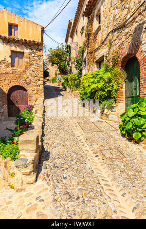 Narrow street with stone houses in old town of Tossa de Mar, Costa Brava, Spain - Stock Photo