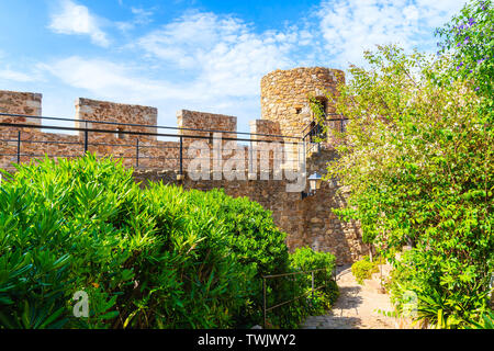 Castle walls and green alley in old town of Tossa de Mar, Costa Brava, Spain - Stock Photo