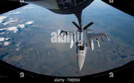 A U.S. Air Force F-16 Fighting Falcon pilot from the 13th Fighter Squadron, Misawa Air Base, Japan, receives fuel from a KC-135 Stratotanker during RED FLAG-Alaska 19-2 near Eielson Air Force Base, Alaska, June 18, 2019. RF-A is an annual U.S. Pacific Air Forces field training exercise for U.S. and international partners to enhance combat readiness of participating forces. The KC-135 is assigned to the 909th Air Refueling Squadron, Kadena Air Base, Japan. (U.S. Air Force photo by Staff Sgt. Matthew Lotz) - Stock Photo