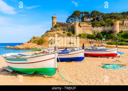 Fishing boats on golden sand beach in bay with castle in background, Tossa de Mar, Costa Brava, Spain - Stock Photo
