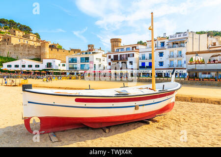 TOSSA DE MAR, SPAIN - JUN 3, 2019: Fishing boat on golden sand beach in Tossa de Mar town with colorful houses in background, Costa Brava, Spain. - Stock Photo