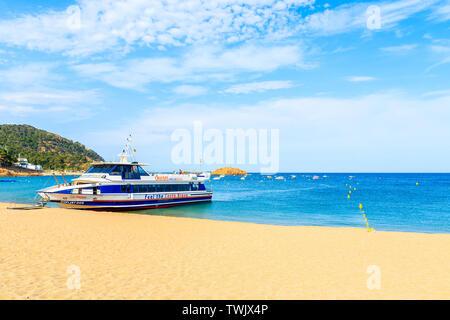 TOSSA DE MAR, SPAIN - JUN 3, 2019: Tourist ship anchoring on golden sand beach in Tossa de Mar town, Costa Brava, Spain. - Stock Photo