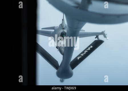 An F-16 Fighting Falcon from the 8th Fighter Wing, Kunsan Air Base, Republic of Korea, prepares to refuel with a KC-135 Stratotanker from the 909th Air Refueling Squadron, Kadena Air Base, Japan, during a training exercise June 18, 2019. The 909th ARS helps ensure a free-and-open Indo-Pacific by providing air refueling to U.S., allies and partners within the area of responsibility. (U.S. Air Force photo by Airman 1st Class Matthew Seefeldt) - Stock Photo