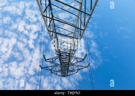 Power lines on metal pillars against a blue sky with clouds, bottom view - Stock Photo