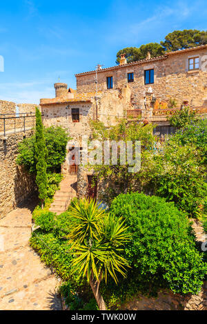 Green tropical plants and stone houses in old town of Tossa de Mar, Costa Brava, Spain - Stock Photo