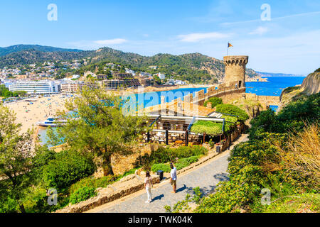 Unidentified young couple of people on castle path taking picture of town and sea, Costa Brava, Spain - Stock Photo