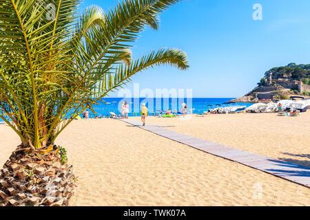 TOSSA DE MAR, SPAIN - JUN 3, 2019: People walking on sandy beach in Tossa de Mar town, Costa Brava, Spain. - Stock Photo