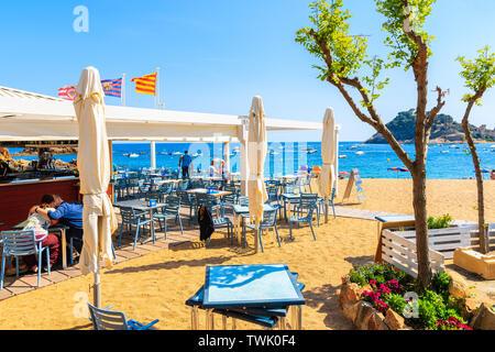 TOSSA DE MAR, SPAIN - JUN 3, 2019: People dining in restaurant on sandy beach in Tossa de Mar town, Costa Brava, Spain. - Stock Photo