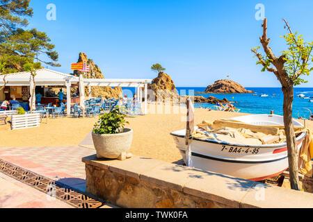 TOSSA DE MAR, SPAIN - JUN 3, 2019: Fishing boat and restaurant on sandy beach in Tossa de Mar town, Costa Brava, Spain. - Stock Photo