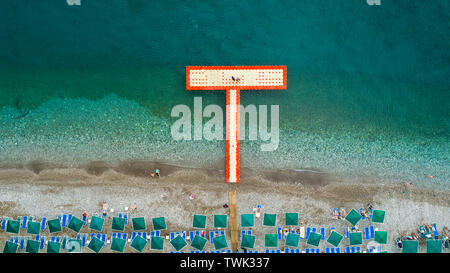 Aerial top view on the beach. Umbrellas, sand and ocean. Aerial top view photo of sun beds in popular tropical paradise deep turquoise mediterranean - Stock Photo