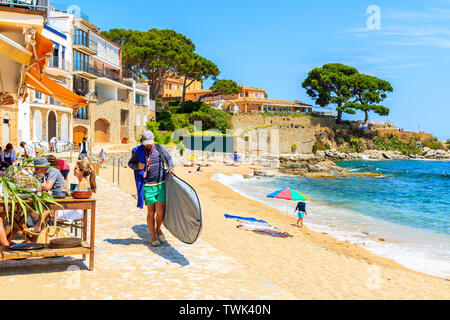CALELLA DE PALAFRUGELL, SPAIN - JUN 6, 2019: Man carrying surfing board to Canadell beach in Calella de Palafrugell village, Costa Brava, Catalonia, S - Stock Photo
