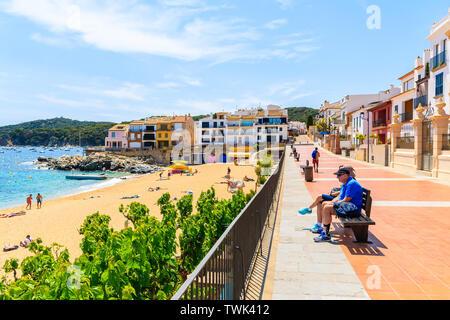 CALELLA DE PALAFRUGELL, SPAIN - JUN 6, 2019: Couple of tourists sitting on beach on coastal promenade near Canadell beach in Calella de Palafrugell vi - Stock Photo