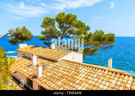 Orange tiles roofs of typical houses on coastal path near Llafranc village, Costa Brava, Spain - Stock Photo