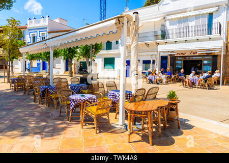 LLAFRANC VILLAGE, SPAIN - JUN 6, 2019: Restaurant tables on street of small fishing village of Llafranc which is located on Costa Brava, Spain. - Stock Photo