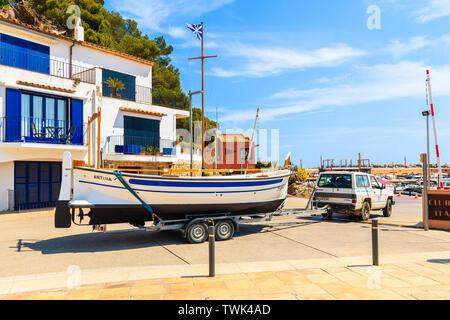 LLAFRANC PORT, SPAIN - JUN 6, 2019: Car transporting fishing boat loaded on a trailer to marina in Llafranc village, Costa Brava, Spain. - Stock Photo
