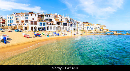CALELLA DE PALAFRUGELL, SPAIN - JUN 6, 2019: Panorama of amazing beach in scenic fishing village with white houses and sandy beach with clear blue wat - Stock Photo