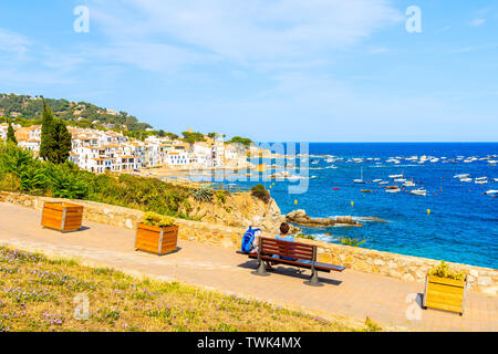 Couple of tourists sitting on coastal promenade in Calella de Palafrugell, scenic fishing village with small castle and sandy beach with clear blue wa - Stock Photo