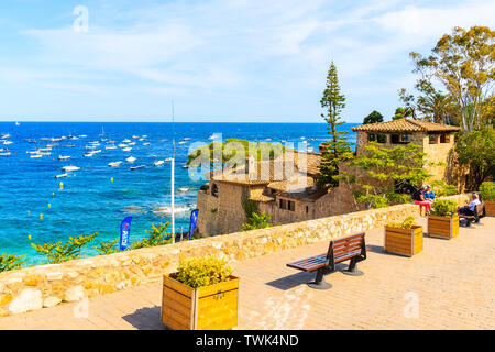 CALELLA DE PALAFRUGELL, SPAIN - JUN 6, 2019: Tourists sitting on coastal promenade in scenic fishing village with small castle and sandy beach with cl - Stock Photo