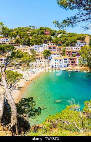 View of colorful houses in sea bay with beach in Sa Tuna coastal village, Costa Brava, Spain - Stock Photo