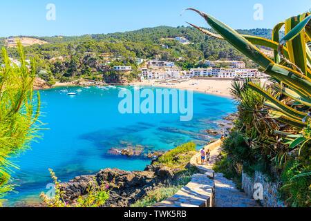 Couple of tourists walking on coastal path to beautiful bay and beach in Sa Riera village, Costa Brava, Spain - Stock Photo
