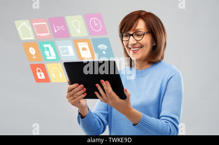 senior woman with tablet pc using smart home app - Stock Photo