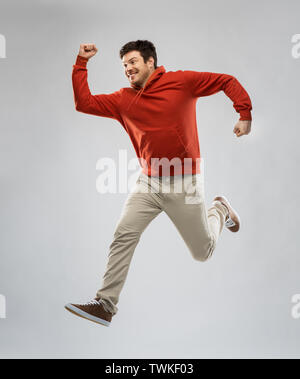 young man in hoodie jumping over grey background - Stock Photo