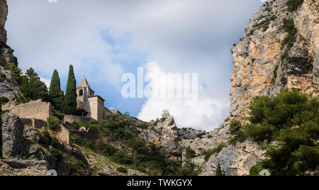 Chapel Notre-Dame-de-Beauvoir perched high on the limestone cliffs above the village of Moustiers-Sainte-Marie in Provence, France. - Stock Photo