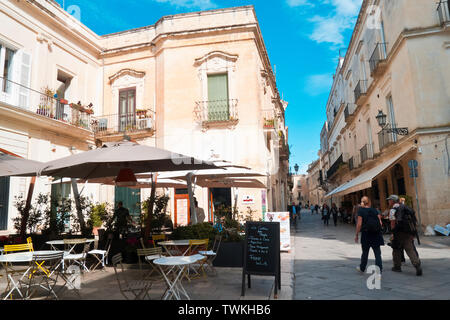 Lecce,Italy,10/10/2016; two travelers with the bags on their shoulder in the street of Lecce,who walk fast and speak in a beautiful autumn morning - Stock Photo