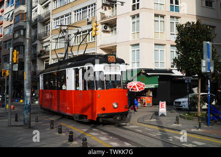 Istanbul, Turkey - February 16, 2019 : A red traditional tram at The Istanbul, Kadikoy with buildings and people in a sunny winter day. Stock Photo