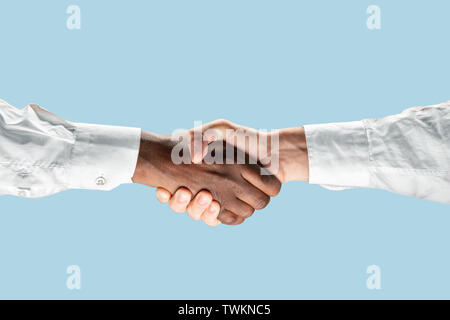 Sign of joint plans for the future. Teamwork and communications. Two male hands shaking isolated on blue studio background. Concept of help, partnership, friendship, relation, business, togetherness. - Stock Photo