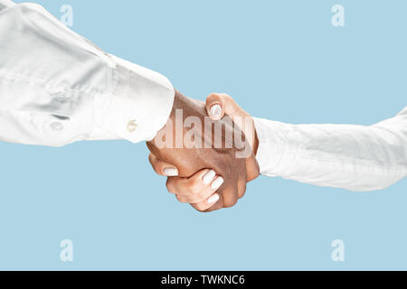 Joint plans for the future. Teamwork and communications. Male and female hands shaking isolated on blue studio background. Concept of help, partnership, friendship, relation, business, togetherness. - Stock Photo