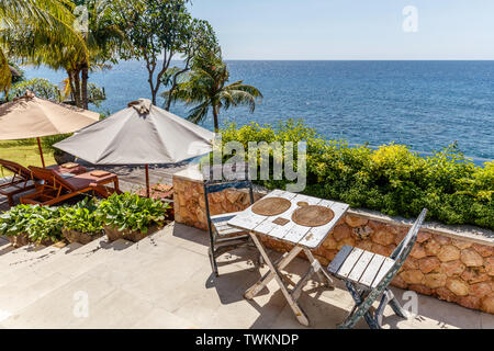 Wooden table and chairs at a outdoor cliff cafe with ocean view, Amed, Karangasem Regency, Bali, Indonesia. - Stock Photo