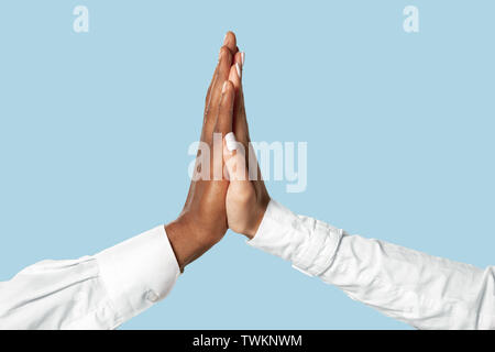Joint plans for the future. Teamwork and communications. Male and female hands touching isolated on blue studio background. Concept of help, partnership, friendship, relation, business, togetherness. - Stock Photo