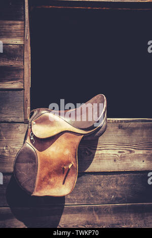 Americana Image Of A Horse Saddle Hanging In A Ranch Stable Door With Copy Space - Stock Photo