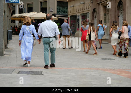 Middle aged couple holding hands while walking down a busy pedestrian walkway in Granada, Spain. - Stock Photo