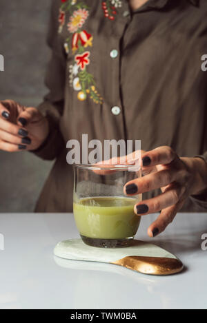 Woman serving detox green juice into glass in the work. Detox cleanse drink concept, green vegetable smoothie ingredients. Natural, organic healthy ju - Stock Photo