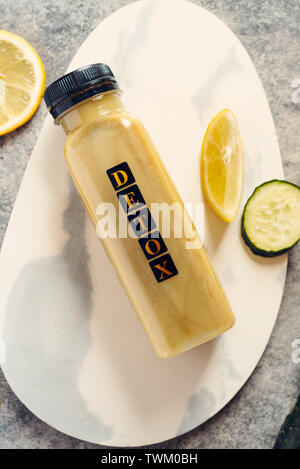 Detox cleanse drink concept, green vegetable smoothie ingredients. Natural, organic healthy juice in bottle for weight loss diet or fasting day. Cucum - Stock Photo