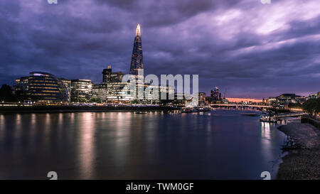 Dusk in London as the sun sets behind a cloudy sky over the Thames. - Stock Photo