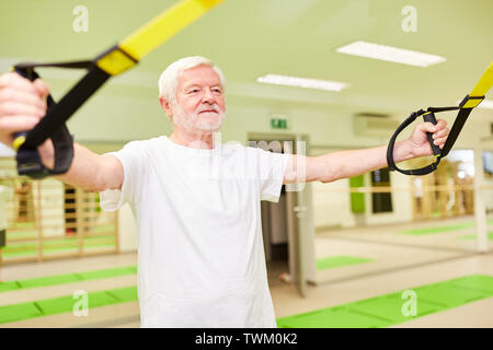 Sporty senior man trains fitness and strength endurance during suspension training - Stock Photo
