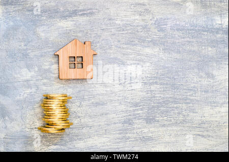 The house symbol is made of bamboo and yellow shiny coins on a scratched concrete gray background. The concept of the offer of purchase of real estate - Stock Photo
