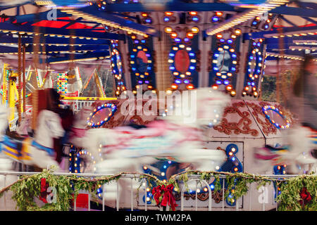 Colorful carousel on traditional holiday Christmas market outdoors. Motion action blur. Merry go round moving fast. Popular winter attraction - Stock Photo