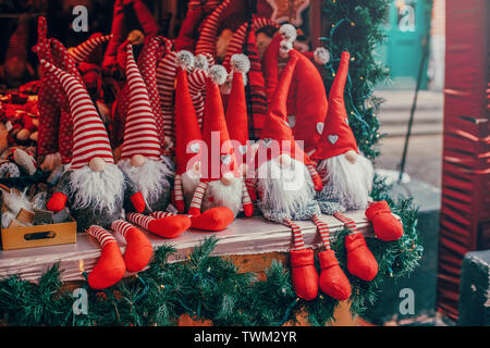 Colorful red toys dwarfs gnomes in red caps hats sitting on counter at traditional holiday Christmas market outdoors. Popular winter attraction - Stock Photo